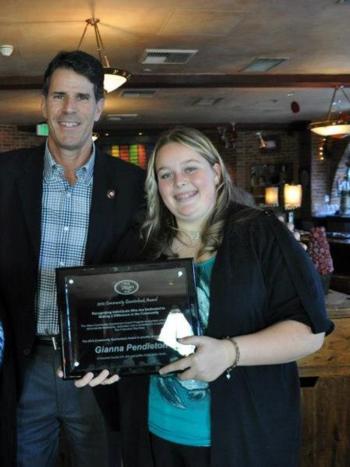 Gianna Pendleton receiving the San Francisco 49ers Community Quarterback Award from Steve Bono, former quarterback of the Niners.